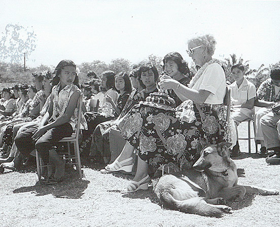 A teacher sitting outdoors with students