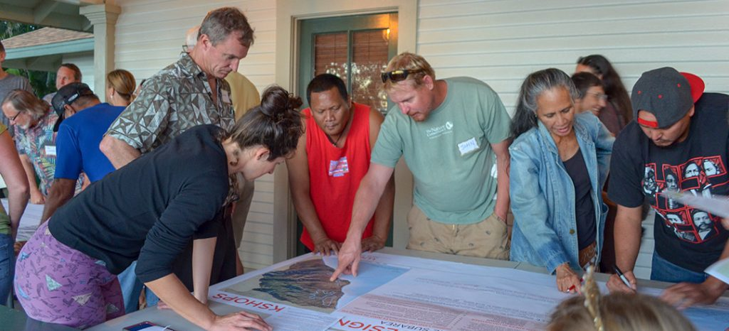 A group gathered around a table to discuss a project on Maui